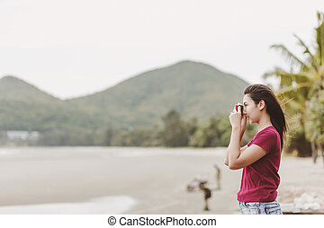 Women use a camera to shot travel on the beach.