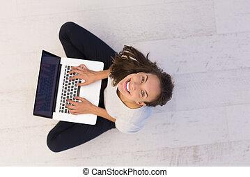 women using laptop computer on the floor top view