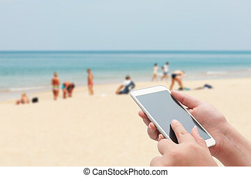 Women using smartphone top on blurred blue sea and white sand beach with some people