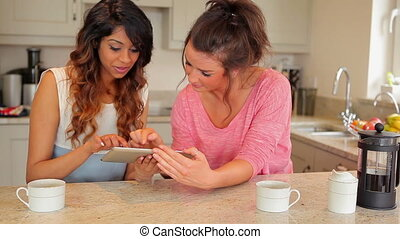 Women using tablet computer drinking coffee in kitchen