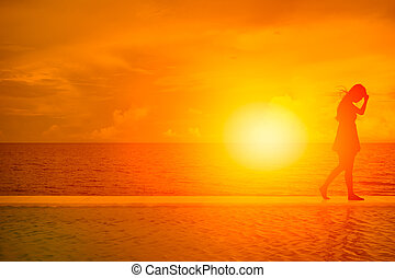 women walk away. silhouette of girl on the beach with summer sea beautiful sunset background