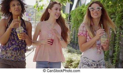 Women walking and having beverages