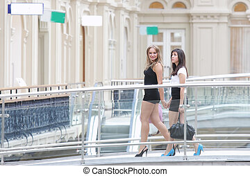 Women walking by bridge in shopping center