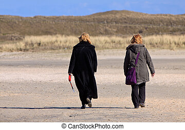 Women walking in the sand dunes on the beach