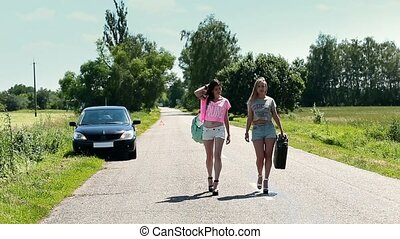 women walking on road with rusty canister in hand