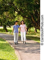 Women Walking Outside - Two Asian women walking in the park...