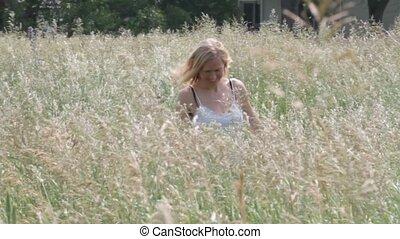 Women walks through grassy Field - Women in sundress walks...