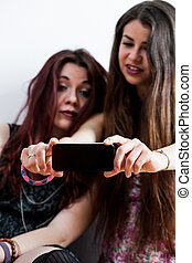 women watching mobile phone or taking a selfie