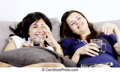 Women watching tv laughing happy