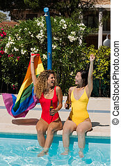 Women waving the rainbow flag at the poolside