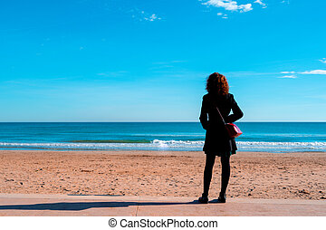 Women wearing autum or winter clothes looking at the sea. Copy space.