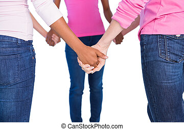 Women wearing pink for breast cancer holding hands