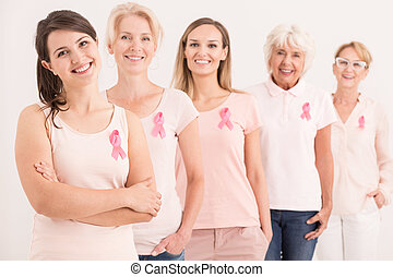 Women wearing pink shirts and cancer ribbons on white...