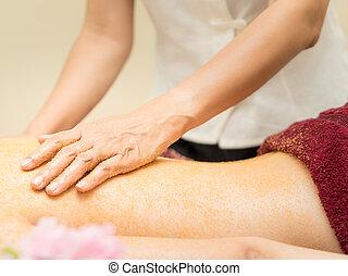 Women wearing red towel is getting back scrub in a Spa