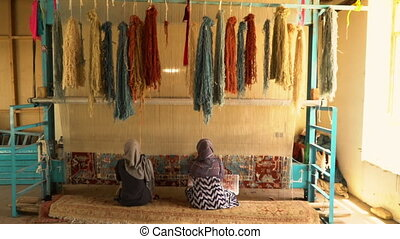 Women weaving factory rugs - A full shot of two women...