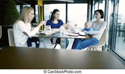 Women with babies in cafe having lunch together. - Three...