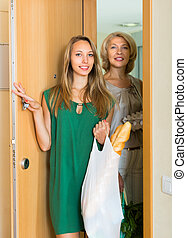 Women with bags of food near door