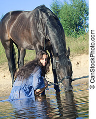 women with black horse in water