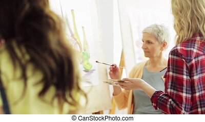 women with brushes painting at art school - creativity,...