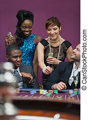 Women with champagne standing at roulette table
