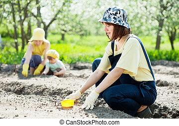 women with child works at garden