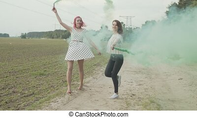 Stylish females walking, hopping and whirling in clouds of colorful smoke on rural road. Happy bright women with colored smoke bombs in hands going joyfully skipping and circling in countryside.
