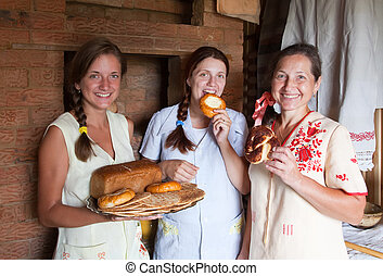 Women with farm-style meal in rural house interior