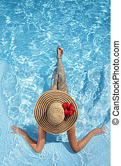 Women with Hat in Pool - Woman sitting in a swimming pool in...