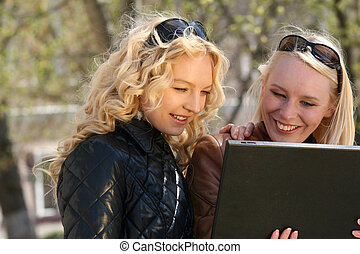 women with laptop in park