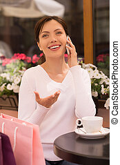 Women with mobile phone. Beautiful young women talking on the mobile phone while sitting at the restaurant