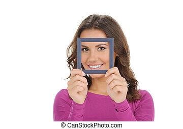 Women with picture frame. Beautiful young women smiling and looking through a picture frame while isolated on white