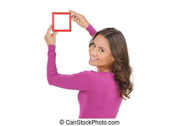 Women with picture frame. Rear view of beautiful young women holding a picture frame and smiling while isolated on white