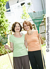 Women with rakes in garden