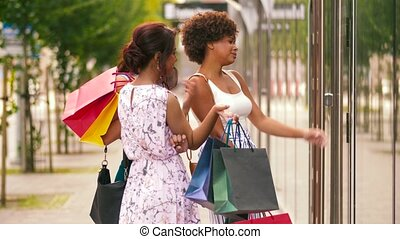 women with shopping bags looking at shop window - sale,...