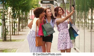 women with shopping bags taking selfie in city - sale,...