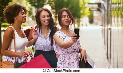 women with shopping bags taking selfie in city