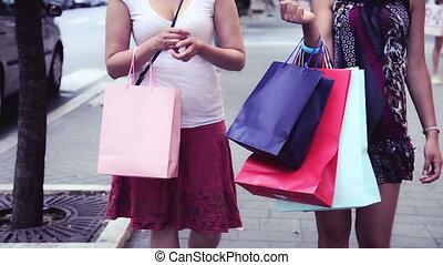 Women with shopping bags walk