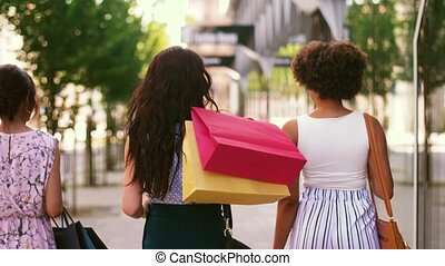 women with shopping bags walking in city - sale, consumerism...