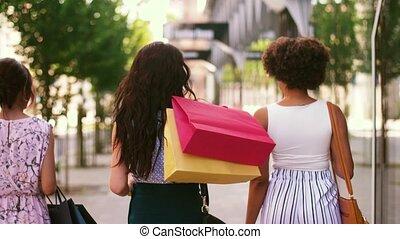 women with shopping bags walking in city