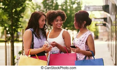 women with smartphones and shopping bags in city - sale,...