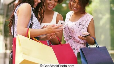 women with smartphones and shopping bags in city