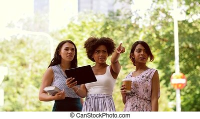 women with tablet pc and city guide on street - tourism,...
