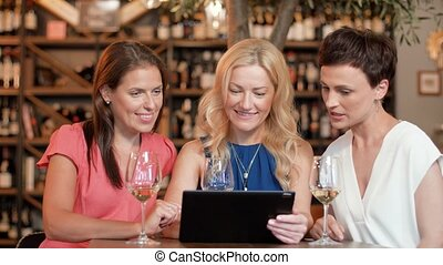 women with tablet pc at bar wine or restaurant - people,...