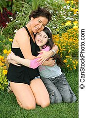 women with teenager sit on grass