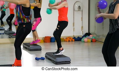 Women working out at the fitness club with stepper and balls in hands