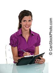 Women writing in her agenda
