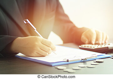 women writing on note book with calculator in morning