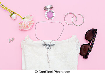 Women's accessories and clothing on a pink background. Flat lay