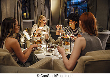 Women's Afternoon Tea - Four women are sitting together...