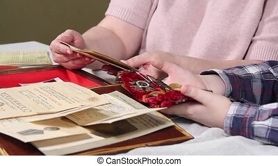 Women's and children's hands are sorting through documents and medals of the Second World War. High quality FullHD footage